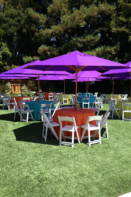 outdoor party table settings under large umbrellas