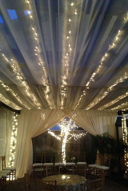outdoor party tent at night with white string lights